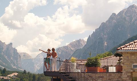 ein Paar steht auf Balkon und betrachtet die Berge