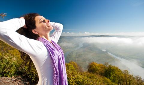 Frau steckt sich, im Hintergrund eine Landschaft