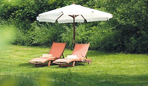 Zwei Liegen in der Wiese mit Sonnenschirm