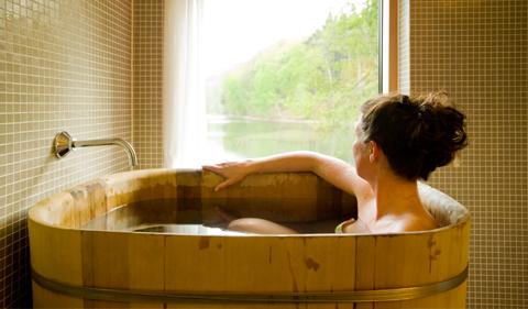 Frau sitzt in hölzener Badewanne und sieht aus dem Fenster